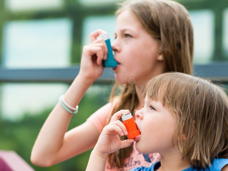 Flickor som har astma genom att använda astmainhalatorn för att vara sunt - sha royaltyfri bild