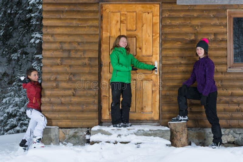 Flickor som har gyckel på en loge i vinter fotografering för bildbyråer