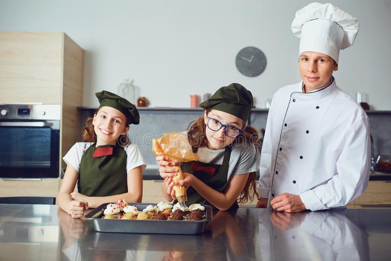 Flickor som hjälper kocken till den dekorerade efterrätten royaltyfri fotografi