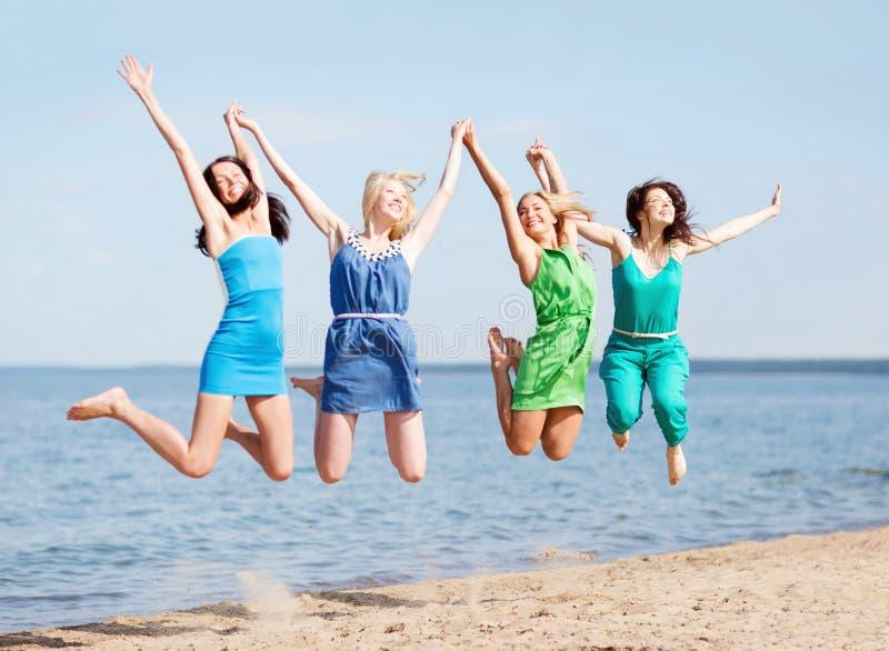 Flickor som hoppar på stranden royaltyfria foton