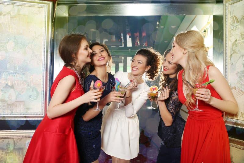 Flickor som klirrar exponeringsglas av coctailar på partiet royaltyfri bild
