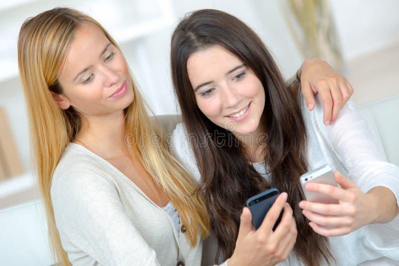 Flickor som kontrollerar den smarta telefonen royaltyfri foto