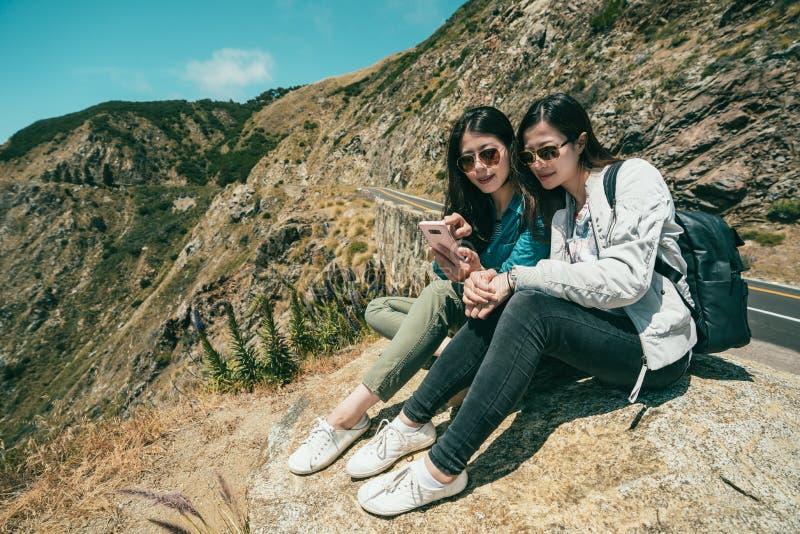 Flickor som kontrollerar telefonen, medan sitta på klippan fotografering för bildbyråer