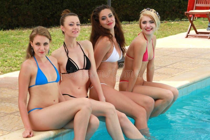 Flickor som kopplar av vid simbassängen royaltyfri bild