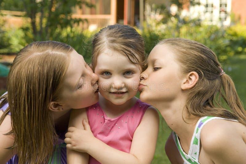 flickor som kysser tre royaltyfri foto