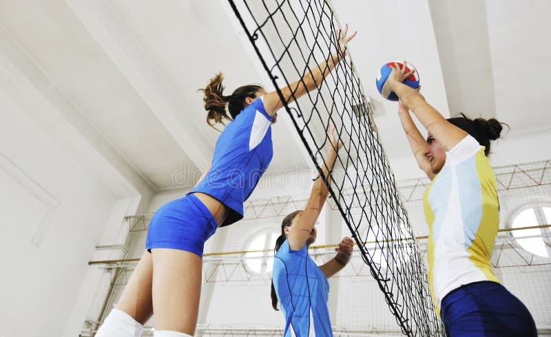 Flickor som leker för volleyboll leken inomhus arkivfoto