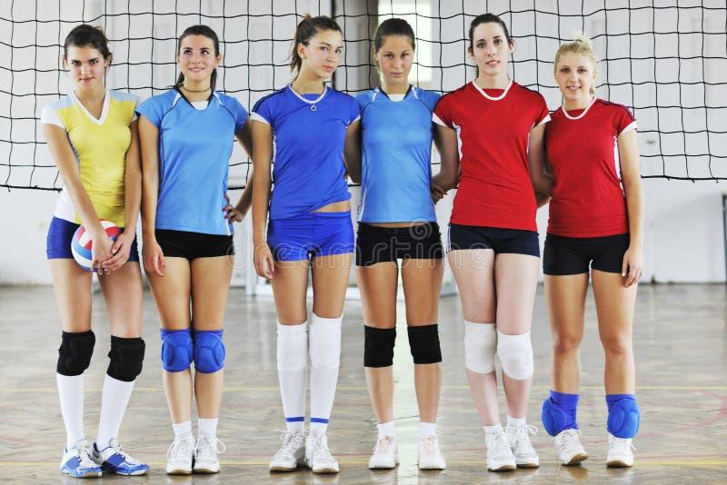 Flickor som leker för volleyboll leken inomhus arkivbild