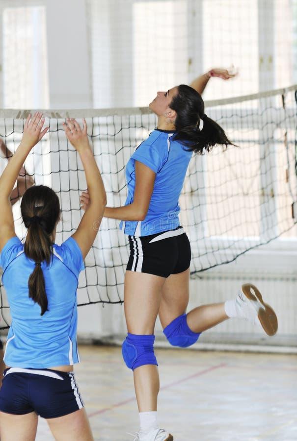 Flickor som leker för volleyboll leken inomhus royaltyfria foton