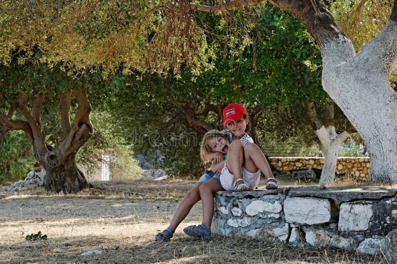 Flickor som leker i fruktträdgård royaltyfria foton