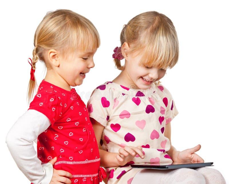 Flickor som leker med en tabletdator arkivbilder