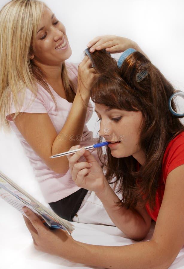 Flickor som leker med hårrullear i långt hår royaltyfria foton