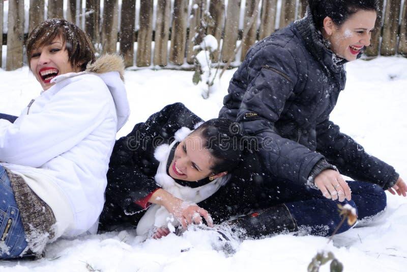 flickor som leker snow tre royaltyfri bild