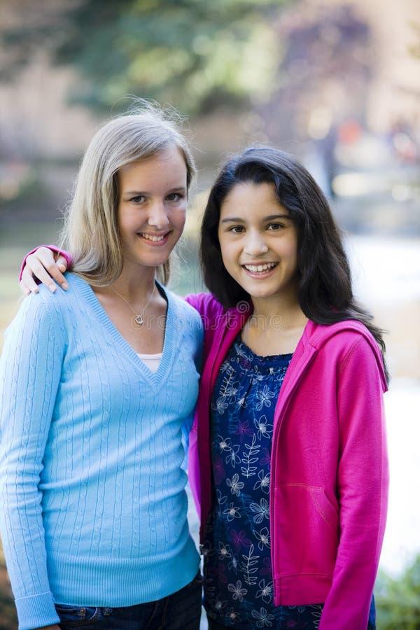 flickor som ler utomhus tween royaltyfri bild