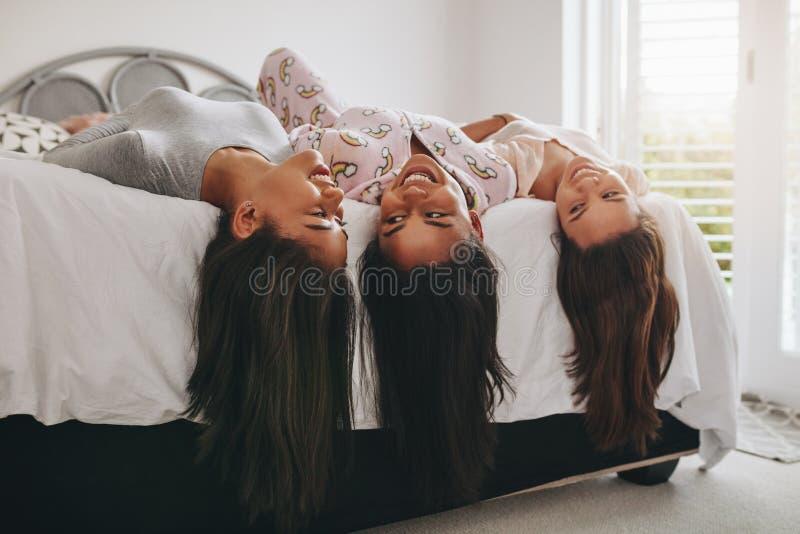Flickor som ligger på säng som har gyckel på en sleepover royaltyfri bild