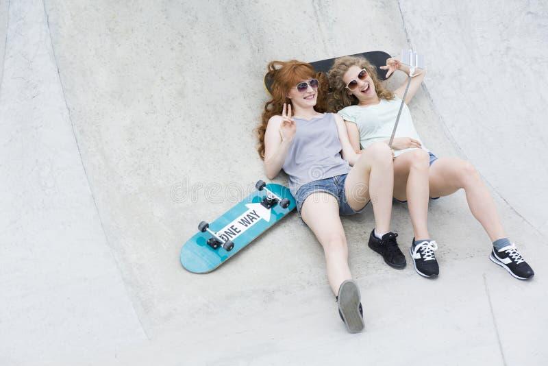 Flickor som ligger på vertrampen och tar selfie royaltyfria foton