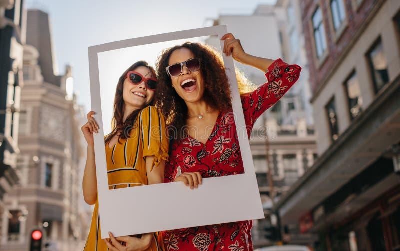 Flickor som poserar med den tomma fotoramen royaltyfria foton