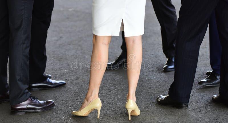 Flickor som precis så är varma som skorna som hon väljer höga skokvinnor för häl Klassiska mäns skor Kvinnlig och manliga ben in royaltyfria bilder