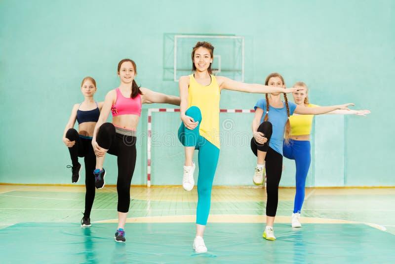 Flickor som rymmer jämvikt under knä-till-bröstkorg elasticitet royaltyfri foto