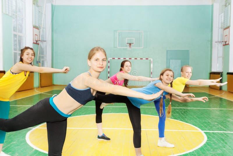 Flickor som rymmer jämviktsanseende på ett ben i idrottshall fotografering för bildbyråer