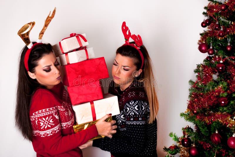 Flickor som rymmer många tunga gåvaaskar bredvid julgranen i tröja- och renhorn royaltyfri bild