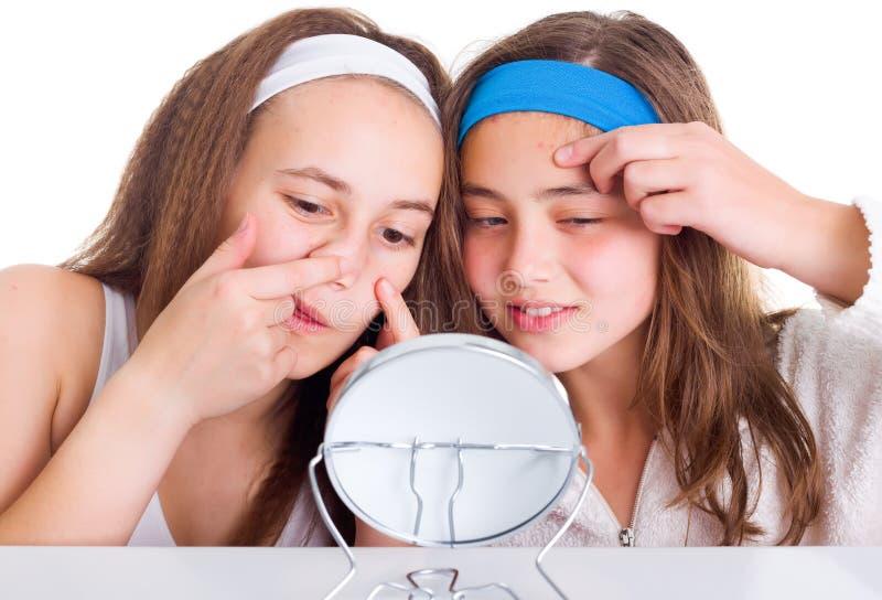 Flickor som söker för skavanker på deras hud arkivfoton