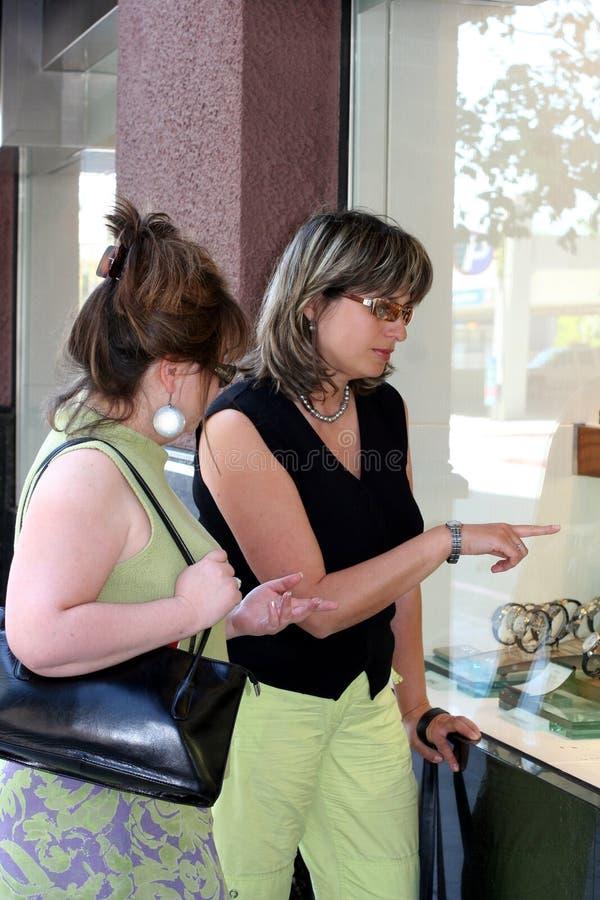 flickor som shoppar fönstret royaltyfri foto