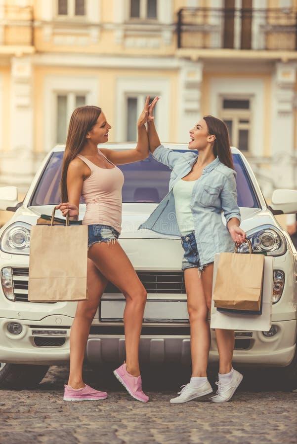 Flickor som shoppar med bilen fotografering för bildbyråer