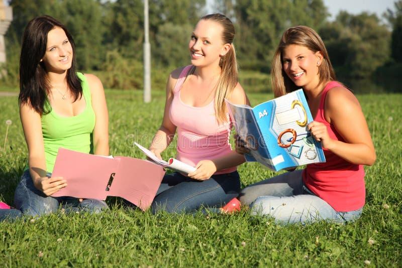 Flickor som sitter i parken och lärer royaltyfri bild