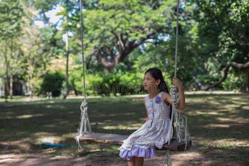 Flickor som sitter i trädgårdgungan arkivbilder