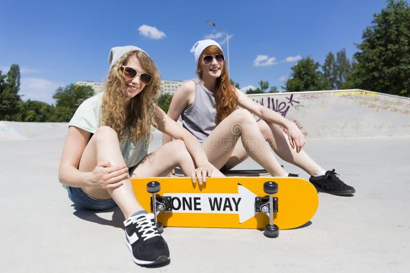 Flickor som sitter på verten, ramp med skateboarden fotografering för bildbyråer