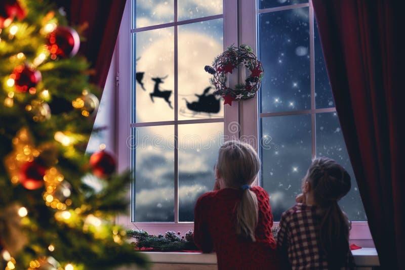 Flickor som sitter vid fönstret och ser jultomten royaltyfri foto