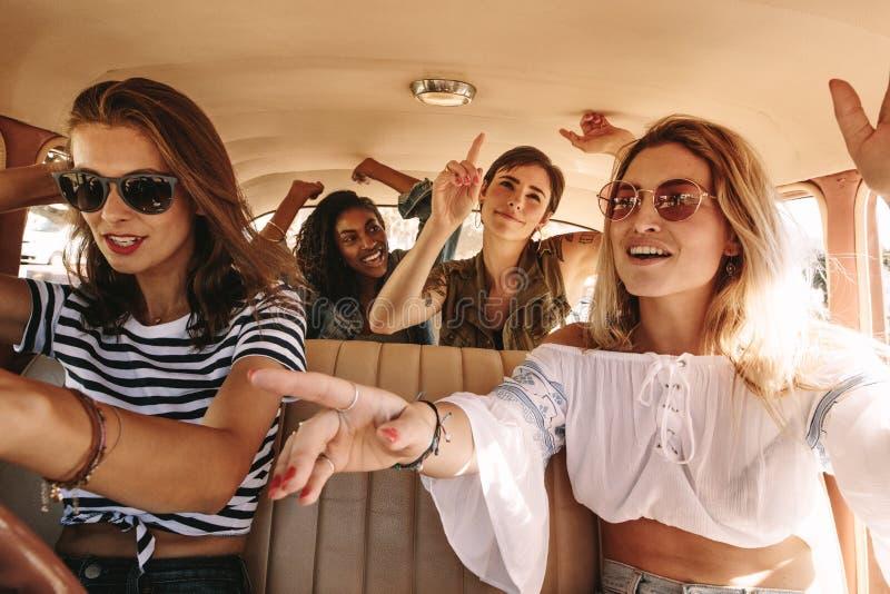 Flickor som sjunger och dansar på stångtur royaltyfria bilder