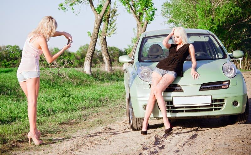 Flickor som skjuter nära en bil arkivbild