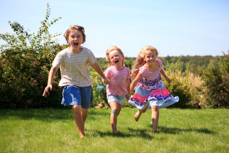 flickor som skrattar utomhus- running tre royaltyfria bilder