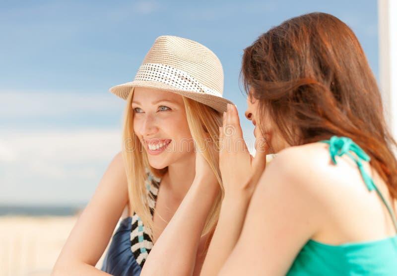 Flickor som skvallrar i kafé på stranden fotografering för bildbyråer