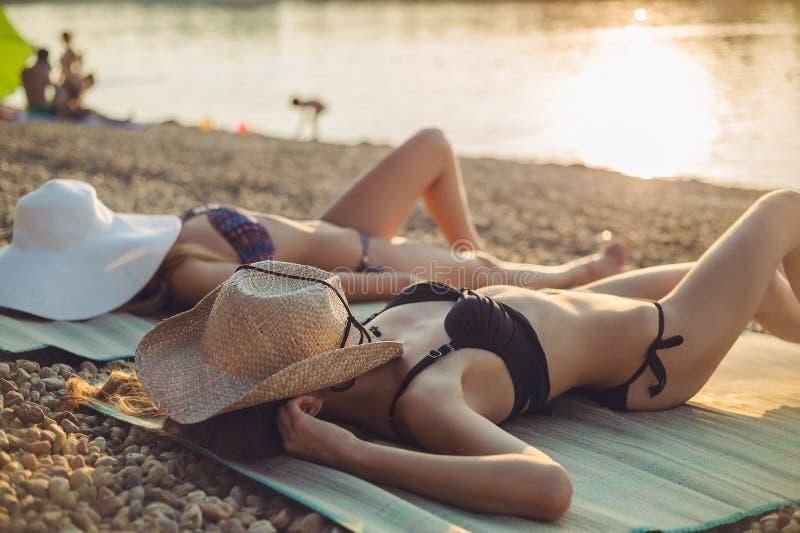 Flickor som sleaping på stranden royaltyfri bild