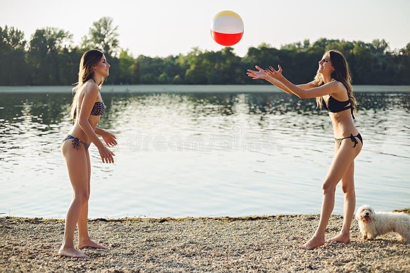 Flickor som spelar med bollen på stranden royaltyfri foto