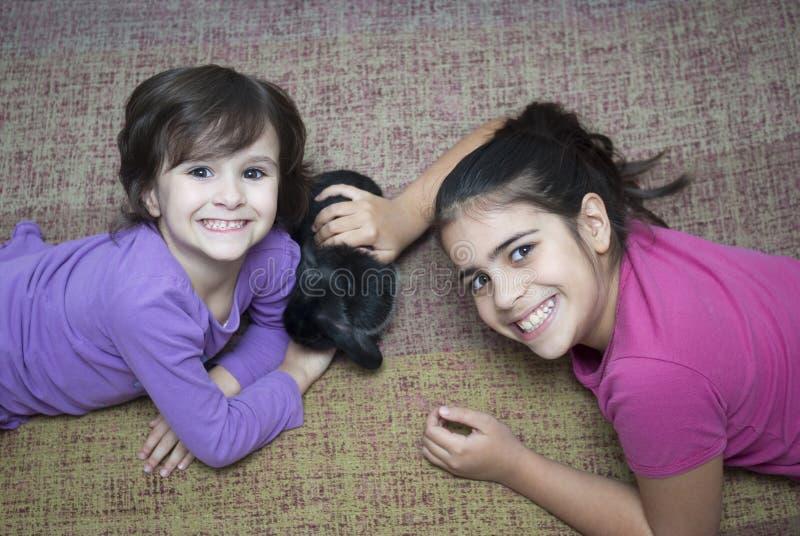 Flickor som spelar med kanin royaltyfria bilder
