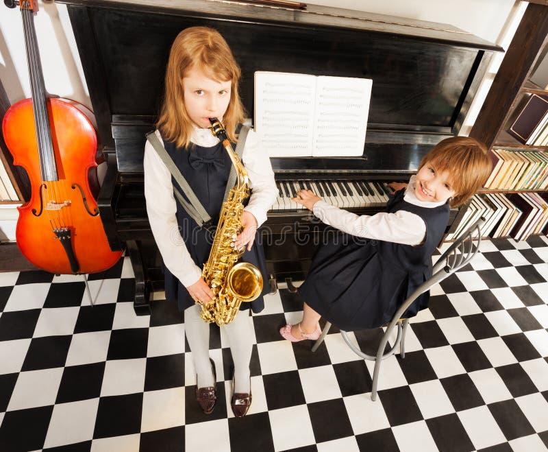 Flickor som spelar på den alt- saxofonen och pianot royaltyfria bilder