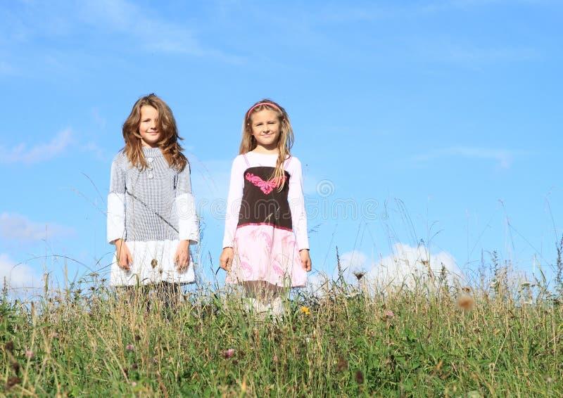 Flickor som står i gräs royaltyfri fotografi