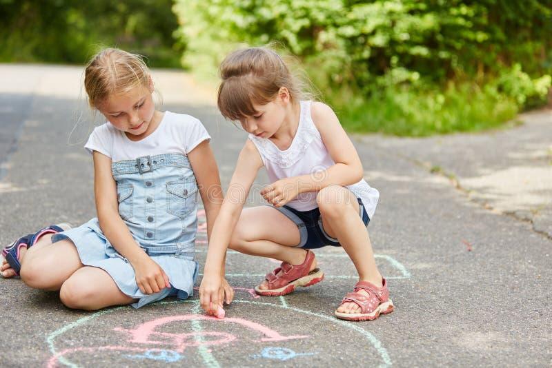 Flickor som systrar målar med krita på golv royaltyfria foton