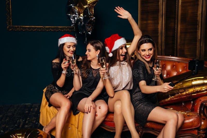 Flickor som tar selfie och, har gyckel på partiet för det nya året royaltyfri fotografi