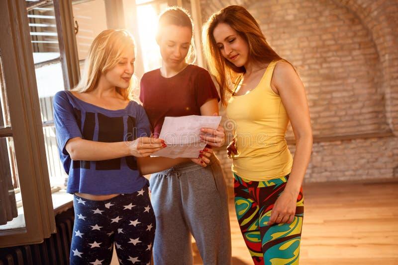 Flickor som tillsammans läser papper inomhus fotografering för bildbyråer