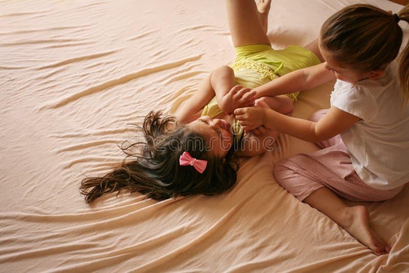 Flickor som tillsammans spelar i säng Två små flickor som hoppar nolla royaltyfri fotografi