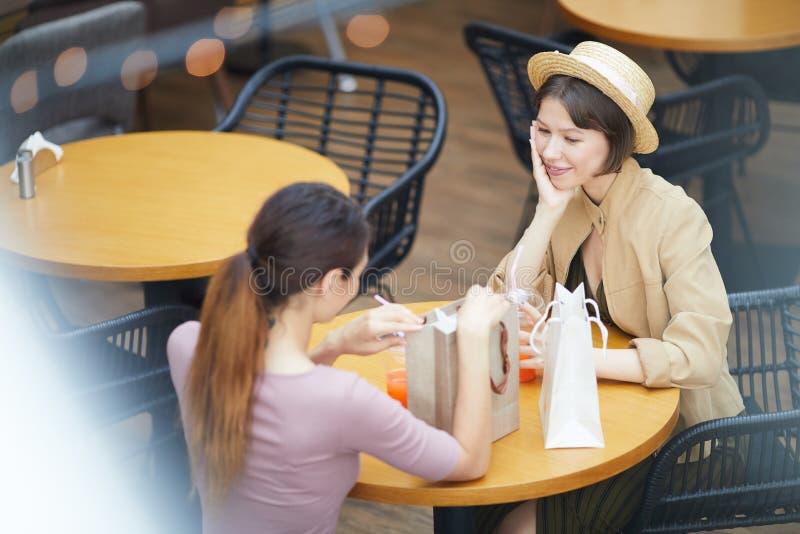 Flickor som utbyter gåvor i kafé arkivbild