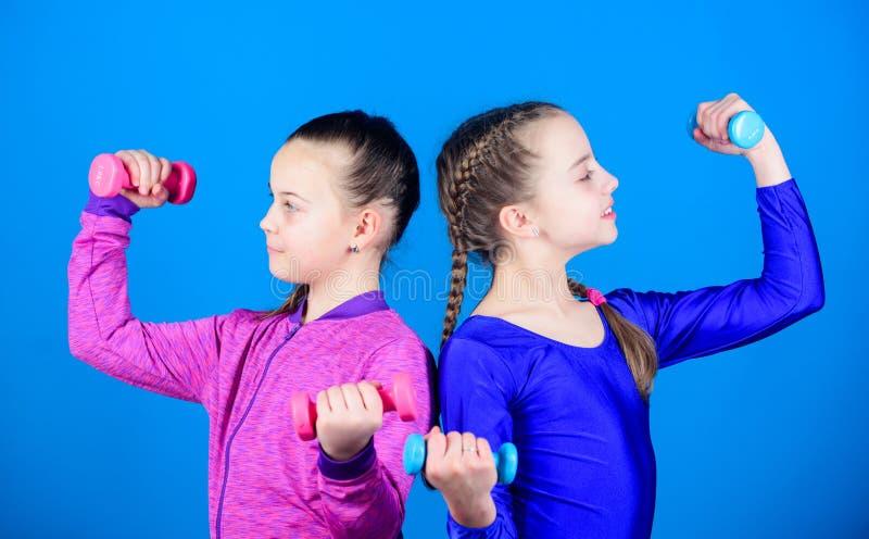Flickor som ?var med hantlar P? v?g till starkare kropp Nyb?rjarehantel?vningar Sportig uppfostran Barn rymmer royaltyfri foto