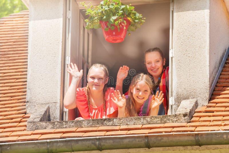 Flickor som vinkar händer som ut ser loftfönstret royaltyfria foton