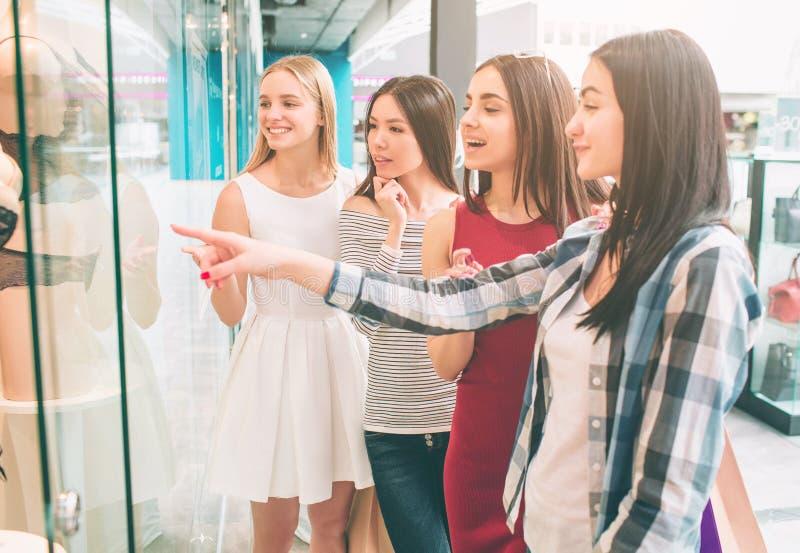 Flickor står på ställa ut av damunderkläderlagret, och se maneken med intressebrunett pekar på royaltyfria foton