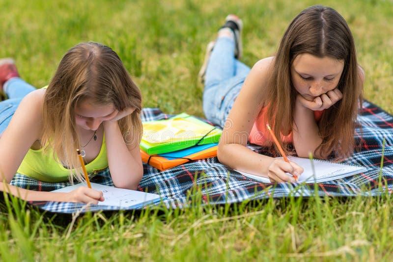 flickor tonårs- två I sommar ligger naturen på en pläd på gräs Han rymmer blyertspennor, och pennor i hans händer, drar in royaltyfria bilder