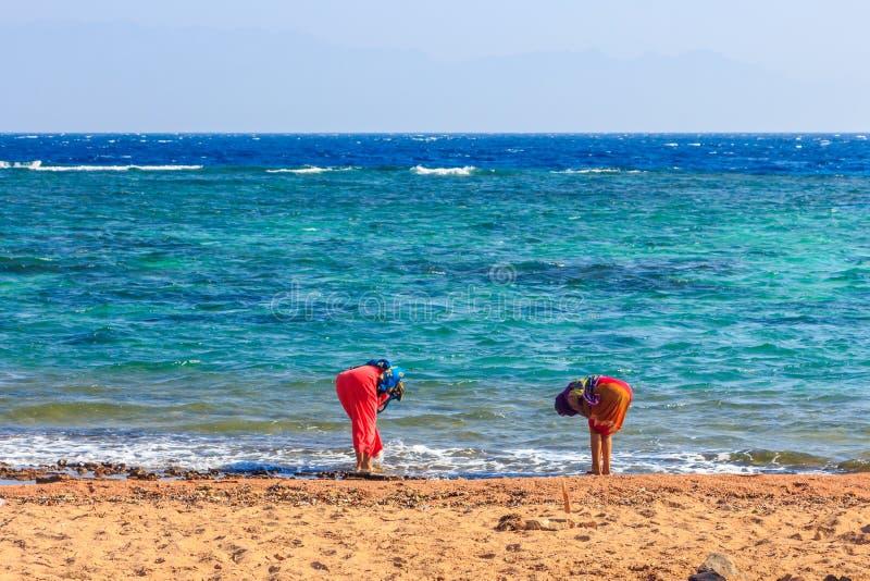Flickor tvättar deras fot i havet royaltyfri foto